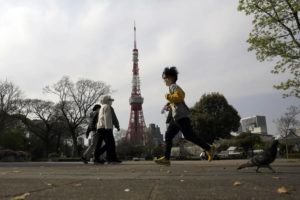 ASSOCIATED PRESS                                 People wearing protective masks walk in the spring weather at Shiba Park in Tokyo as Tokyo Tower loom over in the background.