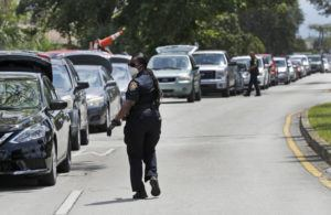 ASSOCIATED PRESS                                 Opa-locka, Fla., police officers controlled traffic at a drive-thru food distribution site at Sherbondy Park, today.