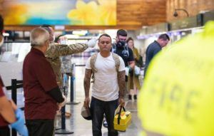 CINDY ELLEN RUSSELL / CRUSSELL@STARADVERTISER.COM                                 Hawaii Army National Guard Spc. Robert Young used an infrared thermometer to take the temperature of a passenger at the Hawaiian Airlines terminal at Daniel K. Inouye International Airport today.