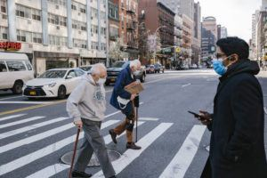 ASSOCIATED PRESS                                 Pedestrians wearing face masks cross the street near Union Square in New York on March 27.