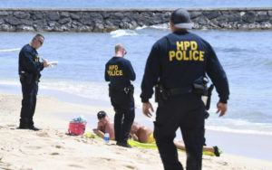 BRUCE ASATO / APRIL 12                                 Enforcement of restrictions of Hawaii beaches continues to increase. Two HPD officers approached sunbathers on Queen's Surf Beach in Waikiki, citing them for violating the emergency stay-at-home order.