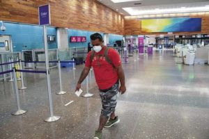 CRAIG T. KOJIMA / APRIL 1                                 Ikaika Picanso walked through an empty Hawaiian Airlines terminal Wednesday at the Daniel K. Inouye International Airport to get to his Big Island flight on April 1.
