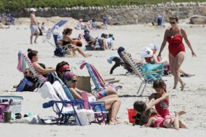 ASSOCIATED PRESS                                 Beachgoers relax on the shore at Good Harbor Beach in Gloucester, Mass., today.