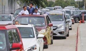 ASSOCIATED PRESS                                 Children use a speaker to pray while waiting with others during a drive-thru Eid al-Fitr celebration outside a closed mosque in Plano, Texas.