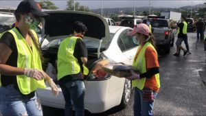 CRAIG T. KOJIMA / CKOJIMA@STARADVERTISER.COM                                 Volunteers distribute free groceries to people in need at the Aloha Stadium parking lot this morning. While Hawaii has effectively flattened the coronavirus infection curve, the economic ramifications of the state's response has left about a third of the workforce unemployed and tens of thousands of people in need of food assistance.