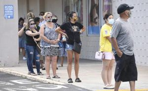 BRUCE ASATO / BASATO@STARADVERTISER.COM Shoppers wearing masks wait in line to get into the Ross Dress for Less Store on South King Street Sunday, which reopened following weeks of closure due to the COVID-19 pandemic. With Hawaii's low coronavirus infection rate, more businesses are reopening, but the state's workforce and economy is still reeling from the shutdown of tourism.