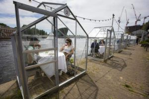 ASSOCIATED PRESS                                 Customers seated in small glasshouses enjoy lunch at the Mediamatic restaurant in Amsterdam, Netherlands, today. The government took a major step to relax the coronavirus lockdown, with bars, restaurants, cinemas and museums reopening under strict conditions, abiding by government guidelines and respecting social distancing to help curb the spread of the COVID-19 coronavirus.