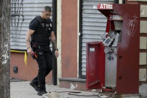 DAVID MAIALETTI/THE PHILADELPHIA INQUIRER VIA AP                                 A member of the Philadelphia bomb squad surveys the scene after an ATM machine was blown-up at 2207 N. 2nd Street in Philadelphia.