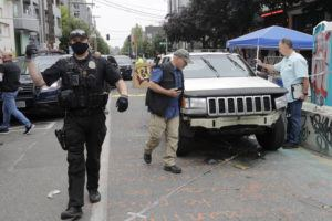 ASSOCIATED PRESS A Seattle police officer asks people to move aside to allow police vehicles through as investigators, right, look over a car involved in a shooting today in Seattle, where streets are blocked off in what has been named the Capitol Hill Occupied Protest zone. One man was killed and another wounded early this morning in the protest zone, the second deadly shooting in the area.