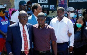 ASSOCIATED PRESS                                 Family attorney Ben Crump, left, escorted Quincy Mason, second from left, a son of George Floyd, today, in Minneapolis, as they and some Floyd family members visited a memorial where Floyd was arrested on May 25 and died while in police custody.