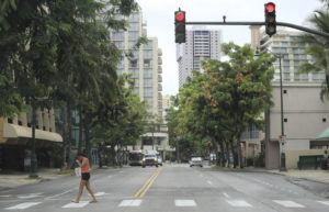 JAMM AQUINO / JULY 30                                 A woman walks across Kuhio Avenue in Waikiki. Though visitor arrivals continue at a steady pace despite the coronavirus pandemic and the 14-day mandatory quarantine, the predicted economic outlook still appears grim.