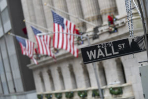 ASSOCIATED PRESS                                 The Wall St. street sign was framed by American flags flying outside the New York Stock Exchange, Jan. 3, in New York. The Federal Reserve said today that American households' net worth jumped nearly 7% in the April-June quarter to $119 trillion.