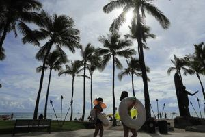 JAMM AQUINO / JAQUINO@STARADVERTISER.COM                                 People pass the Duke Kahanamoku statue on Friday in Waikiki. The state's highly anticipated pre-travel COVID-19 testing program that launched Thursday drew over 10,000 travelers on its first day.