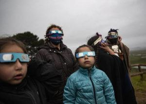 ASSOCIATED PRESS                                 A Mapuche Indigenous family uses special glasses to try and observe a total solar eclipse in Carahue, La Araucania, Chile. The total eclipse was not visible from Carahue because of an overcast sky.