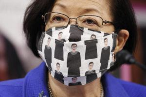 ASSOCIATED PRESS / OCTOBER 12 Sen. Mazie Hirono, D-Hawaii, wears a mask showing former Supreme Court Justice Ruth Bader Ginsburg during a confirmation hearing for Supreme Court nominee Amy Coney Barrett before the Senate Judiciary Committee, on Capitol Hill in Washington.