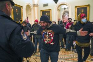 ASSOCIATED PRESS / JAN. 6                                 Trump supporters gesture to U.S. Capitol Police in the hallway outside of the Senate chamber at the Capitol in Washington.