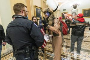 ASSOCIATED PRESS / JAN. 6                                 Supporters of President Donald Trump are confronted by U.S. Capitol Police officers outside the Senate Chamber inside the Capitol in Washington. An Arizona man seen in photos and video of the mob wearing a fur hat with horns was also charged Saturday in Wednesday's chaos. Jacob Anthony Chansley, who also goes by the name Jake Angeli, was taken into custody Saturday, Jan. 9.