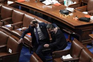 ASSOCIATED PRESS Lawmakers evacuate the floor as protesters try to break into the House Chamber at the U.S. Capitol today in Washington.