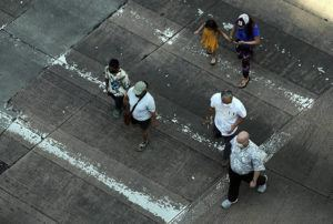 JAMM AQUINO / FEB. 2                                 Pedestrians with face masks cross Hotel Street earlier this month in downtown Honolulu.