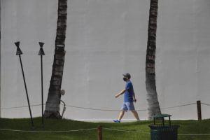 CINDY ELLEN RUSSELL / FEB. 17                                 A masked pedestrian walks along Kalakaua Avenue in Waikiki on Wednesday, Feb. 17.