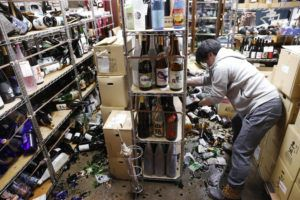 ASSOCIATED PRESS A liquor shop's manager clears the damaged bottles following an earthquake late Saturday night in Fukushima, northeastern Japan.