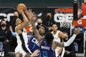 ASSOCIATED PRESS                                 San Antonio Spurs forward Keldon Johnson, left, shoots over Charlotte Hornets guard Malik Monk (1) and forward Miles Bridges during the second half of an NBA basketball game in Charlotte, N.C., on Sunday.