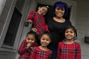 ASSOCIATED PRESS                                 Dinora Torres, a MassBay Community College student, poses with her four daughters on the front porch of their home in Milford, Mass. From front left are daughters Davina, Alana and Hope, with Faith in Dinora's arms. At the college, applications for meal assistance scholarships have increased 80% since last year. Among the recipients is Torres, who said the program helped keep her enrolled.