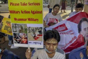 ASSOCIATED PRESS                                 An anti-coup protester holds a placard requesting military action against Myanmar military in Yangon, Myanmar, Thursday.