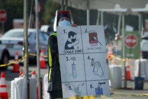 ASSOCIATED PRESS                                 A worker gives instructions to motorists at a COVID-19 testing site in Los Angeles.