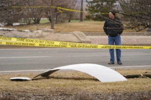 ASSOCIATED PRESS                                 A piece of debris from a passenger airplane is surrounded by police tape on a strip along Midway Boulevard in Broomfield, Colo., after the plane shed parts while making an emergency landing at nearby Denver International Airport.