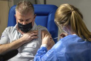 ASSOCIATED PRESS                                 A healthcare worker administers a dose of the AstraZeneca COVID-19 vaccine to a Brussels police chief inspector Didier Bruer at the Brussels Expo center in Brussels today. The Expo is one of the largest vaccination centers in Belgium.
