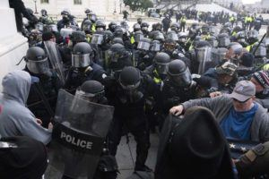 ASSOCIATED PRESS                                 U.S. Capitol Police pushed back rioters trying to enter the U.S. Capitol, Jan. 6, in Washington. A former State Department aide in President Donald Trump's administration has been charged with participating in the deadly siege at the Capitol.