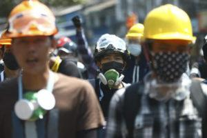 ASSOCIATED PRESS                                 Anti-coup protesters wearing helmets and masks take positions as police gather in Yangon, Myanmar, Friday.