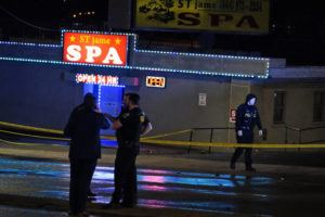 ASSOCIATED PRESS                                 Law enforcement officials confer outside a massage parlor following a shooting today, in Atlanta.