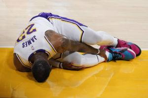 ASSOCIATED PRESS                                 Los Angeles Lakers forward LeBron James holds his ankle after going down with an injury during the first half of an NBA basketball game against the Atlanta Hawks in Los Angeles.