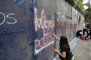 "ASSOCIATED PRESS                                 A young woman spray paints ""The police killed her"" in Spanish on the perimeter wall of the Quintana Roo state offices during a protest in Mexico City, today."