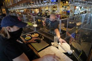 ASSOCIATED PRESS                                 Bartender Daniel Vazquez, right, paces a plate to Betsy Campbell as she eats lunch at Picos Mexican restaurant in Houston. Picos, like many restaurants across the state, continue to operate at a reduced capacity and ask customers to wear masks despite Texas Gov. Greg Abbott ending state mandates for COVID-19 safety measures.