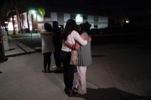 ASSOCIATED PRESS                                 Unidentified people comfort each other as they stand near a business building where a shooting occurred in Orange, Calif., today.