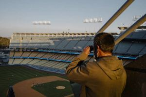 NEW YORK TIMES                                 A baseball fan uses binoculars during a game between the Los Angeles Dodgers and the Los Angeles Angels at Dodger Stadium, Monday.