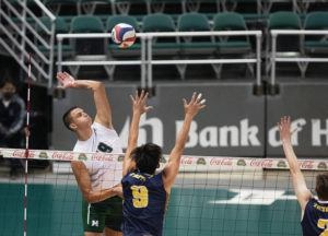 CINDY ELLEN RUSSELL / CRUSSELL@STARADVERTISER.COM                                 Hawaii opposite Rado Parapunov rose for a kill as UC San Diego outside hitter Ryan Ka (9) went to block during the first set of Friday's match at the SimpliFi Arena at Stan Sheriff Center.