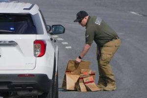 ASSOCIATED PRESS                                 A sheriff's deputy from Frederick County, Md., put paper bags with evidence into a police vehicle near the scene of a shooting at a business park in Frederick, Md., today.