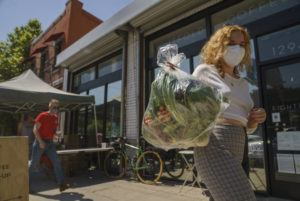 ASSOCIATED PRESS                                 Fashion designer Josie Vand wears a facemask as she retrieves a bag with organic vegetables from a farm box from County Line Harvest in Los Angeles on April 2. California has been easing COVID-19 restrictions as it recovers from a deadly winter surge, although public health officials still urge people to follow social distancing and mask-wearing protocols. Rates of hospitalizations and deaths have plunged, and the rate of people testing positive for the virus is at a near-record low.