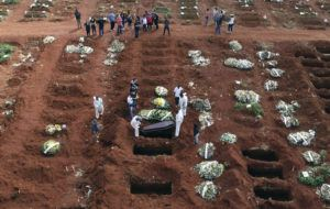 ASSOCIATED PRESS                                 Cemetery workers wearing protective gear lowered the coffin of a person who died from complications related to COVID-19 into a gravesite, Wednesday, at the Vila Formosa cemetery in Sao Paulo, Brazil. Nations around the world set new records, today, for COVID-19 deaths and new coronavirus infections, and the disease surged even in some countries that have kept the virus in check.