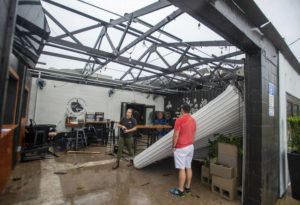 JOHN BLACKIE/PENSACOLA NEWS JOURNAL VIA AP                                 Employees assess the damage after the storm that came through Pensacola, Fla., and blew the roof off of Emerald Republic Brewing.