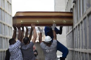 ASSOCIATED PRESS                                 The remains of a woman who died from complications related to COVID-19 are placed into a niche by cemetery workers and relatives at the Inahuma cemetery in Rio de Janeiro, Brazil, on Tuesday.