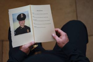 ASSOCIATED PRESS / FEBRUARY 3                                 A U.S. Capitol Police officer holds a program during a ceremony memorializing U.S. Capitol Police officer Brian Sicknick, as an urn with his cremated remains lies in honor on a black-draped table at the center of the Capitol Rotunda in Washington.