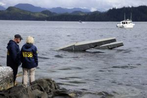 ASSOCIATED PRESS                                 In this photo provided by the National Transportation Safety Board, NTSB investigator Clint Crookshanks, left, and member Jennifer Homendy stand near the site of some of the wreckage of the DHC-2 Beaver, Wednesday, May 15, 2019, that was involved in a midair collision near Ketchikan, Alaska, a couple of days earlier. The pilots of two Alaskan sightseeing planes that collided in midair couldn't see the other aircraft because airplane structures or a passenger blocked their views, and they didn't get electronic alerts about close aircraft because safety systems weren't working properly. That's what the staff of the National Transportation Safety board found in their investigation.