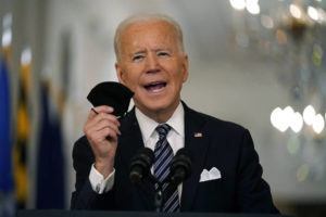 ASSOCIATED PRESS                                 President Joe Biden held up his face mask, March 11, as he spoke about the COVID-19 pandemic during a prime-time address from the East Room of the White House in Washington. The White House is trying to overcome diminishing demand for COVID-19 shots by offering businesses a tax incentive to give employees paid leave to get vaccinated.