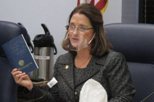 ASSOCIATED PRESS                                 Alaska state Sen. Lora Reinbold, an Eagle River Republican, holds a copy of the Alaska Constitution during a committee hearing in Juneau, Alaska, in January. Alaska Airlines has banned the Alaska state senator for refusing to follow mask requirements. Last week Reinbold was recorded in Juneau International Airport arguing with Alaska Airlines staff about mask policies. A video posted to social media appears to show airline staff telling Reinbold her mask must cover her nose and mouth. Reinbold has been a vocal opponent to COVID-19 mitigation measures and has repeatedly objected to Alaska Airlines' mask policy, which was enacted before the federal government's mandate this year.