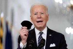 ASSOCIATED PRESS                                 President Joe Biden held up his mask, March 11, as he spoke about the COVID-19 pandemic during a prime-time address from the East Room of the White House in Washington. Biden spent his first 100 days in office encouraging Americans to mask up and stay home to slow the spread of the coronavirus.